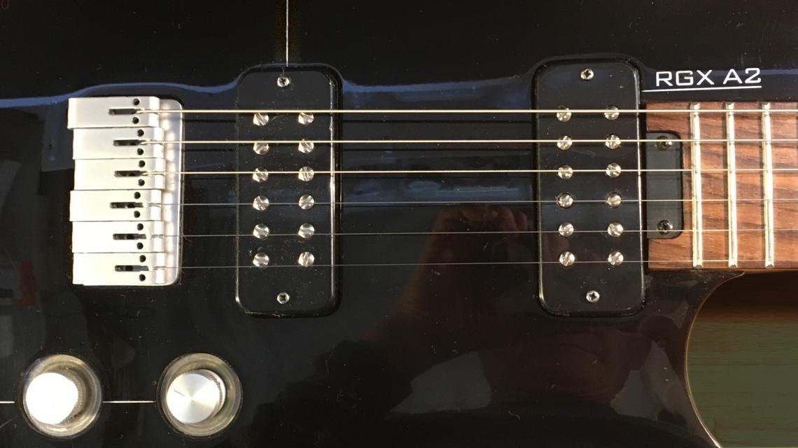Close up of the RGX A2 showing the name, two pickups bridge and two controls