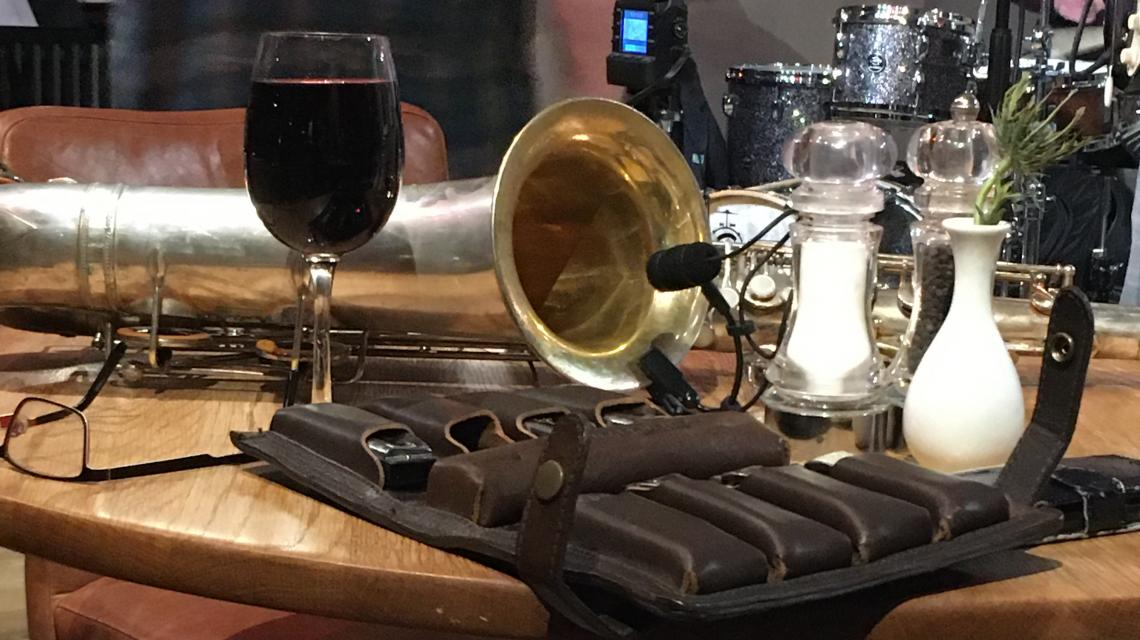 saxophone, blues harmonicas and a glass of wine on a pub table